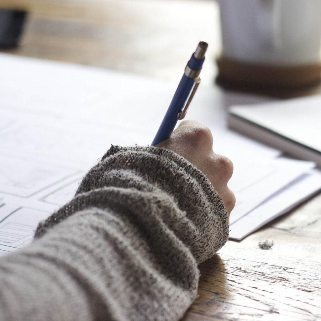 Käsi, joka pitelee kynää pöydän päällä, jossa on papereita.