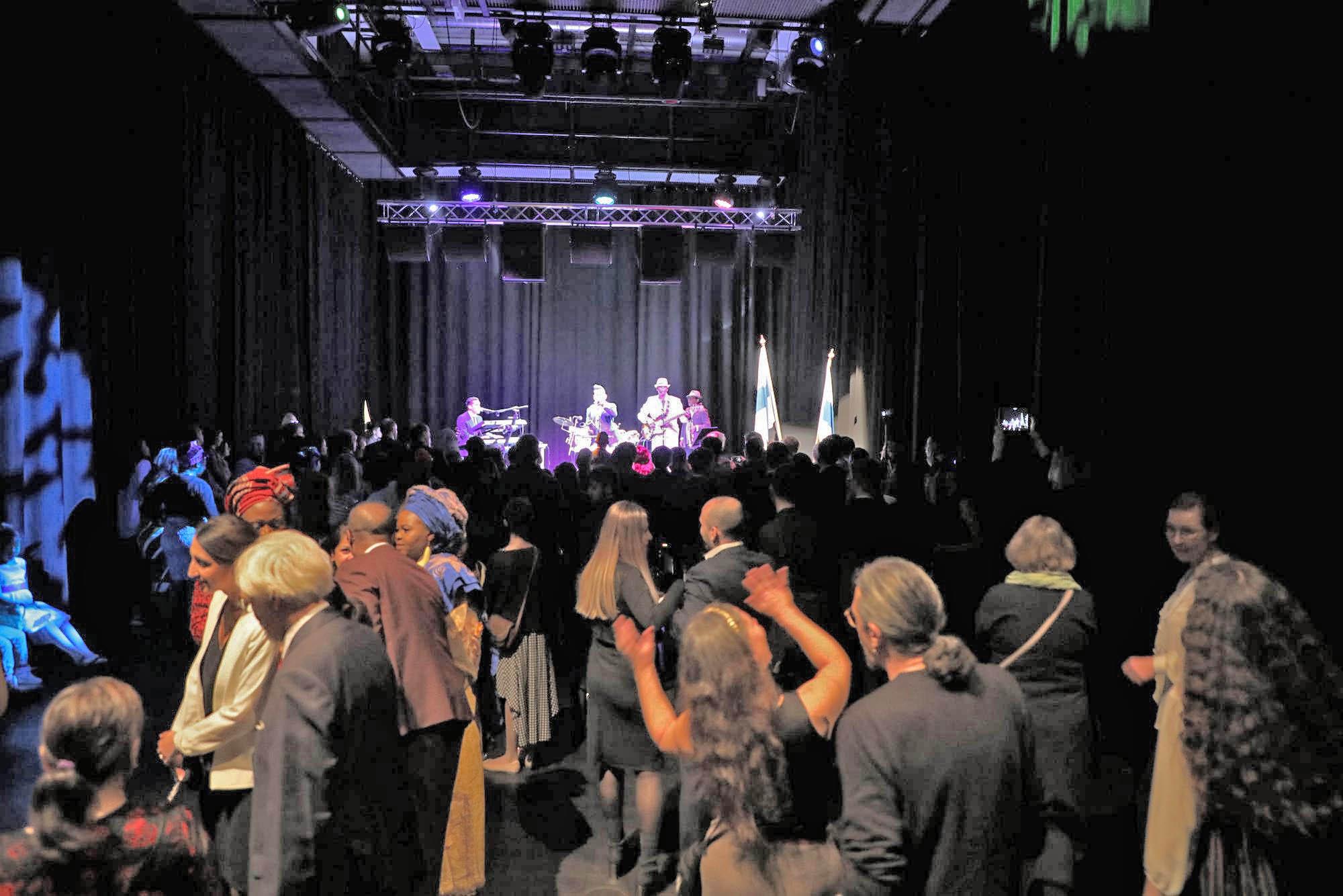 Monikulttuurisen itsenäisyyspäiväjuhlan osallistujia, taustalla musiikkiesitys lavalla.