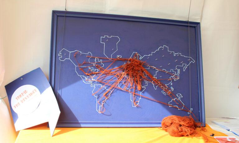 Pöydällä on taulu maailmankartasta, jossa on langalla yhdistetty paikkoja.
