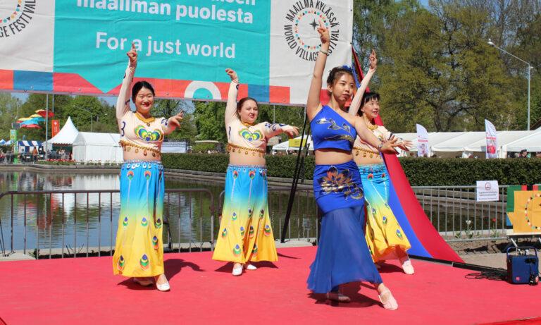 Neljä tanssijaa esiintymässä Maailma kylässä -festivaaleilla.
